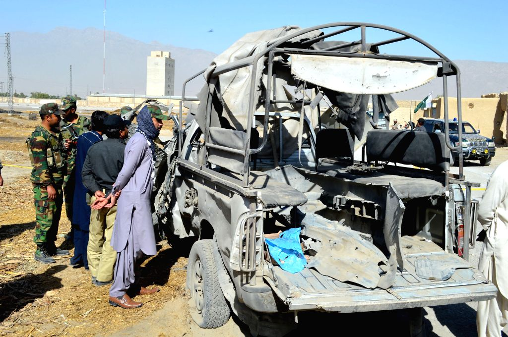 QUETTA, May 19, 2016 - People gather around a destroyed police vehicle at the blast site in Quetta, southwest Pakistan, May 19, 2016. At least one policeman was killed and five others were injured ...