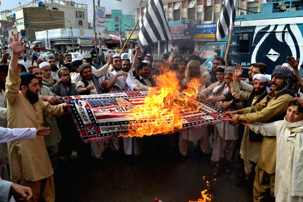 Pakistani protester burn a US flag as they shout slogans during a protest on the third anniversary of the death of slain Al-Qaeda leader Osama bin Laden, in southwest .