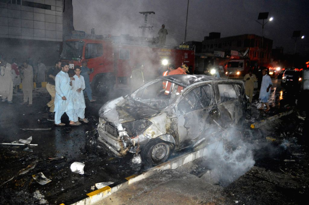 QUETTA, Oct. 16, 2019 - Security officials inspect a burnt vehicle at the blast site in Quetta, Pakistan, Oct. 15, 2019. One policeman was killed and 10 others were injured when a roadside bomb hit a ...