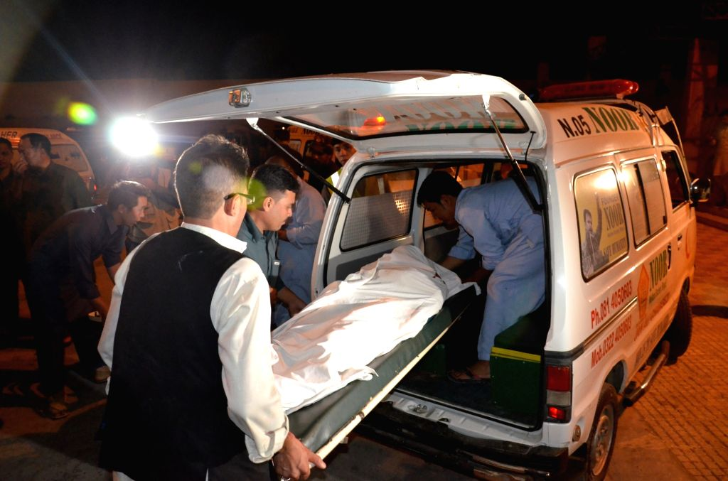 QUETTA, Oct. 4, 2016 - People transfer a body to a hospital in southwest Pakistan's Quetta on Oct. 4, 2016. At least four female passengers were killed when unidentified gunmen opened fire on a bus ...