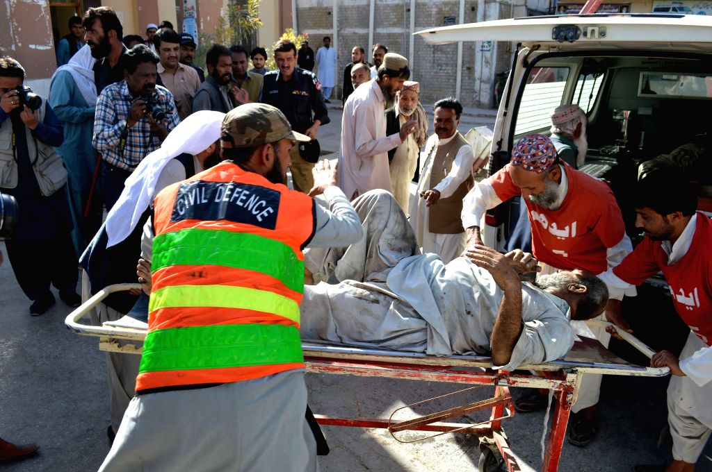 QUETTA, Oct. 7, 2016 - People transfer an injured man to a hospital in Quetta, Pakistan, Oct. 7, 2016. At least four people were killed and 16 others injured when twin blasts hit a passenger train in ...