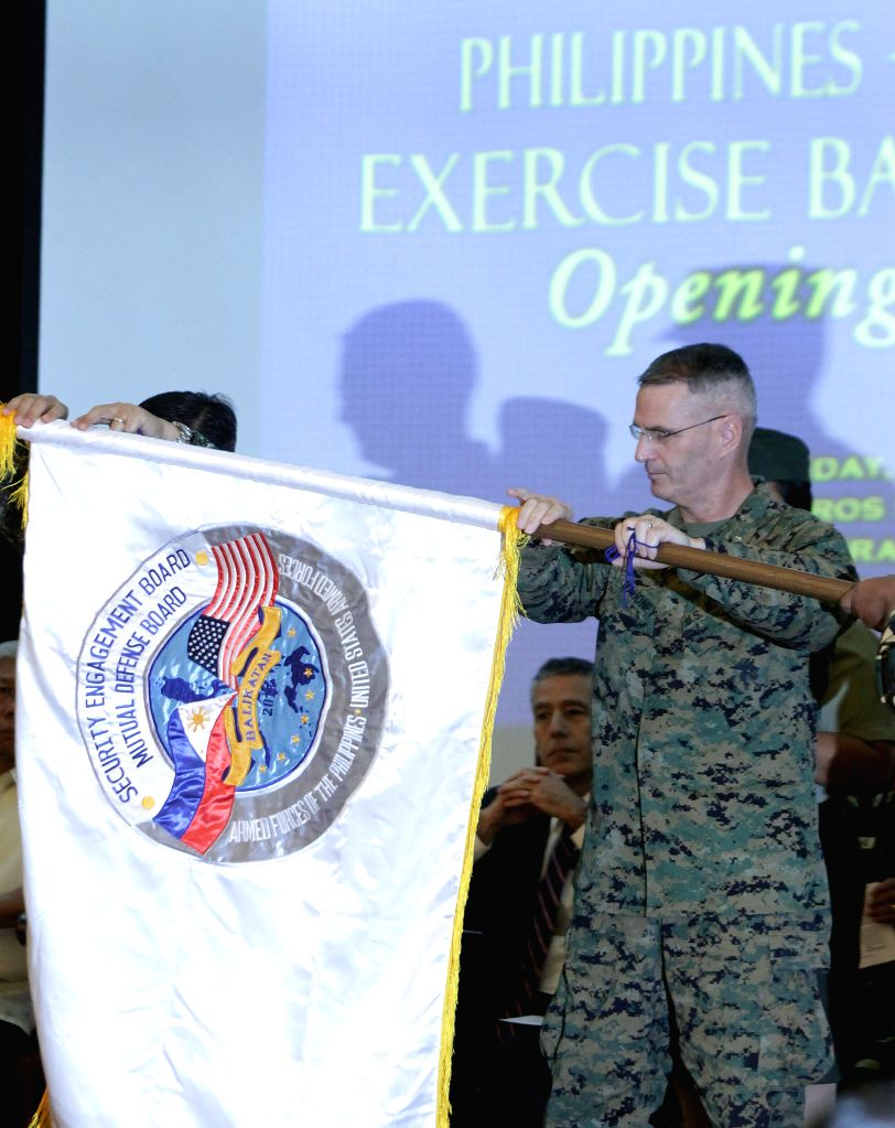 U.S. Marine Corps Brigadier General Christopher J. Mahoney unfolds the official flag of the Balikatan Exercise between the Philippines and the United States ...
