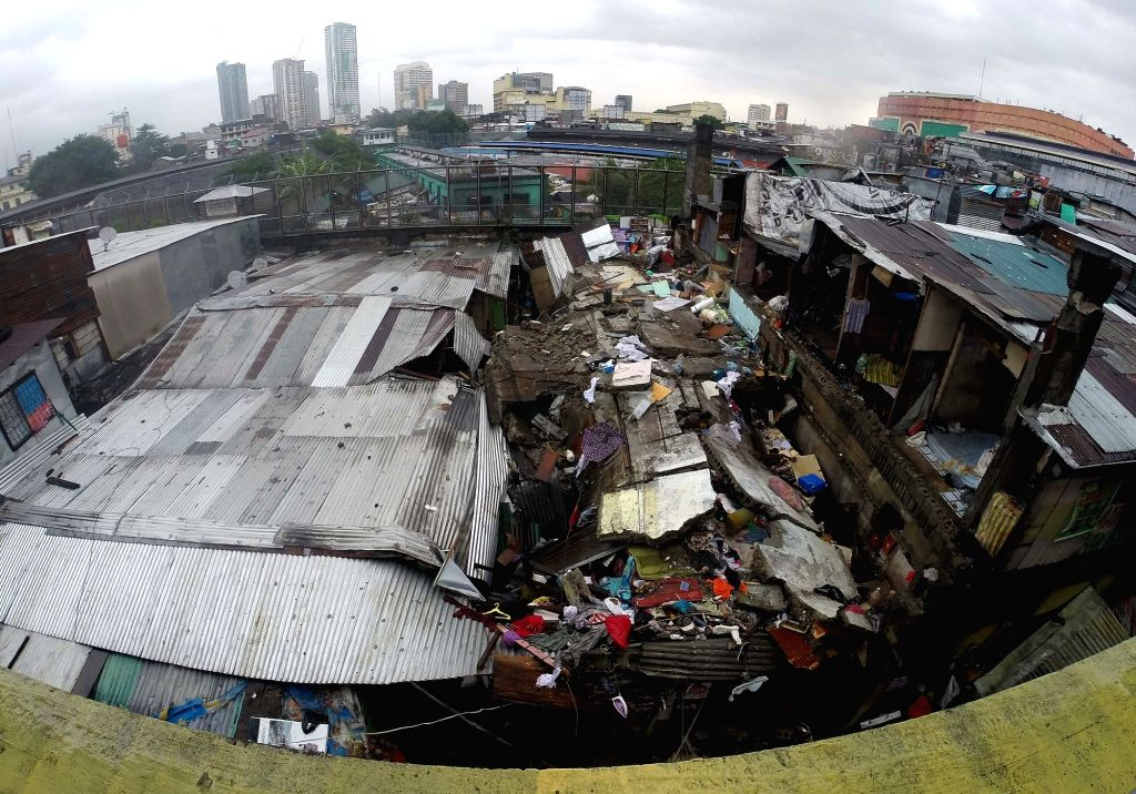 QUEZON CITY, Aug. 13, 2016 - Photo taken on Aug. 13, 2016 shows shanties crushed under a collapsed concrete wall at a slum area in Manila, the Philippines. The concrete wall collapsed on shanties ...