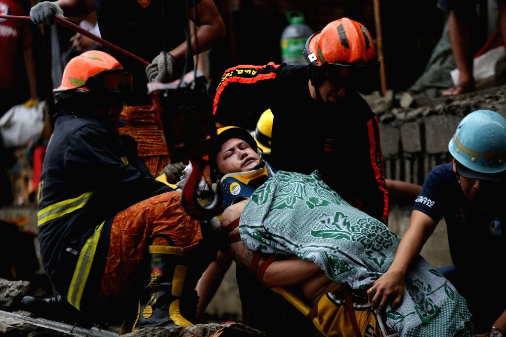 QUEZON CITY, Aug. 13, 2016 - Rescuers carry a man found in the rubbles of a concrete wall at a slum area in Manila, the Philippines, Aug. 13, 2016. The concrete wall collapsed on shanties where four ...