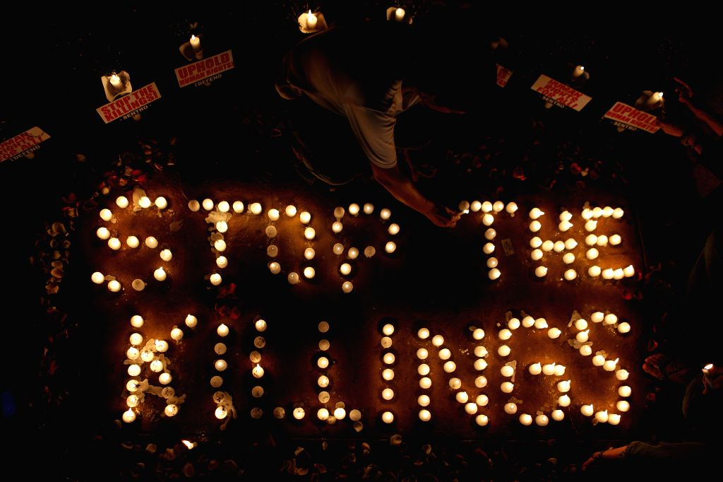 """QUEZON CITY, Aug. 15, 2016 - An activist lights candles that spell out """"Stop the Killings"""" to denounce the extra-judicial killings against alleged suspects involved in illegal drugs during ..."""