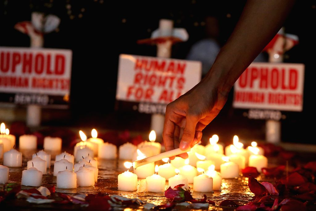 QUEZON CITY, Aug. 15, 2016 - An activist lights candles to denounce the extra-judicial killings against alleged suspects involved in illegal drugs during a protest rally in Quezon City, the ...
