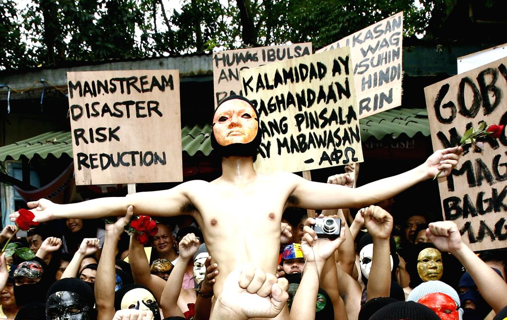 """The crowd cheer as a naked student member of the Alpha Phi Omega fraternity is lifted by his colleagues during the 36th annual """"oblation run"""" to ."""