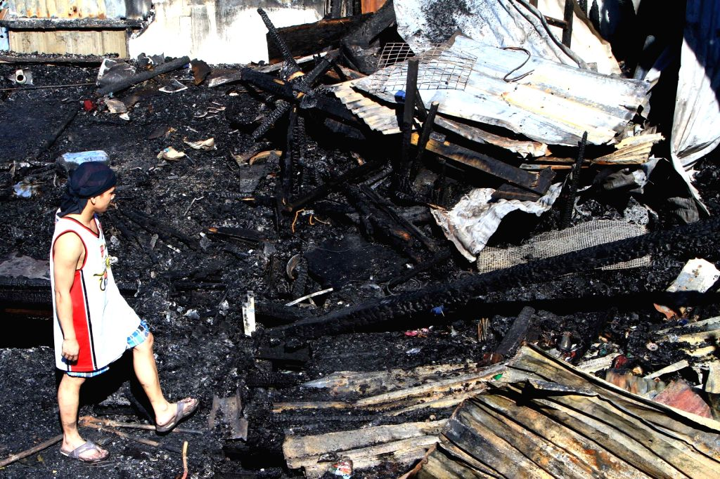 A resident walks on his burnt burnt home after a fire engulfed a residential area in Quezon City, the Philippines, Dec. 14, 2013. About 200 families were ..