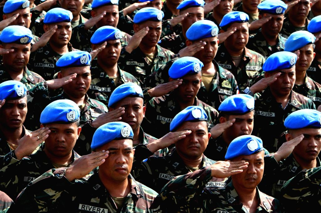 Soldiers from the UN Peacekeepers of the Armed Forces of the Philippines (AFP) salute during the celebration of the 78th anniversary of AFP at Camp ...