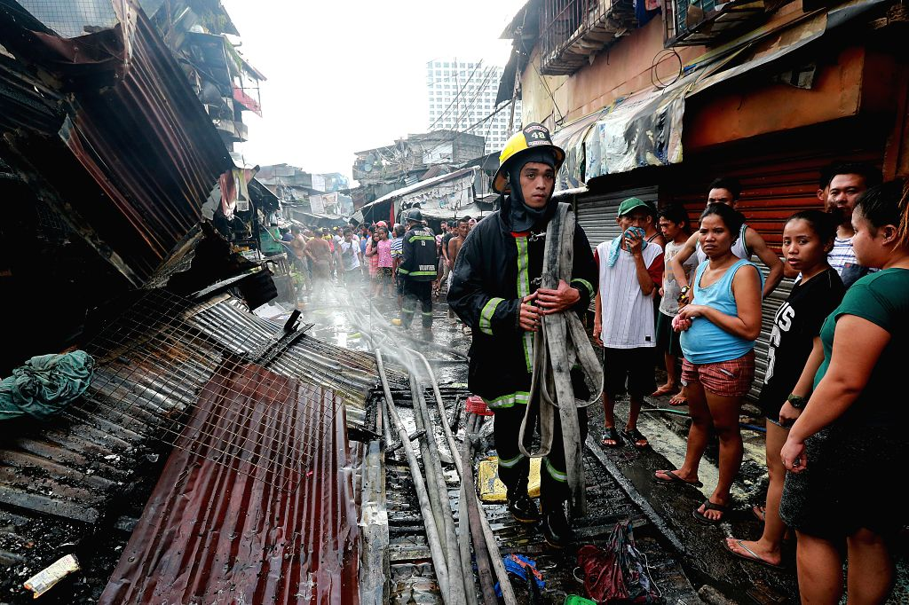 QUEZON CITY, Feb. 9, 2019 - A firefighter carries a water hose after putting out a fire that broke out at a slum area in Quezon City, the Philippines, Feb. 9, 2019. More than 100 shanties were razed ...