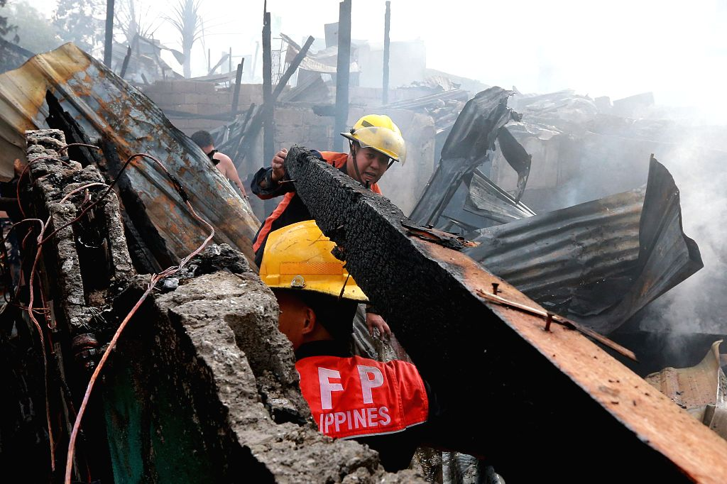 QUEZON CITY, Feb. 9, 2019 - Firefighters clear out debris as they try to put out a fire that broke out at a slum area in Quezon City, the Philippines, Feb. 9, 2019. More than 100 shanties were razed ...