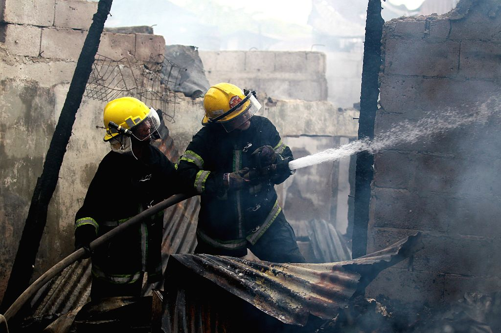 QUEZON CITY, Feb. 9, 2019 - Firefighters try to put out a fire that broke out at a slum area in Quezon City, the Philippines, Feb. 9, 2019. More than 100 shanties were razed in the fire, leaving ...