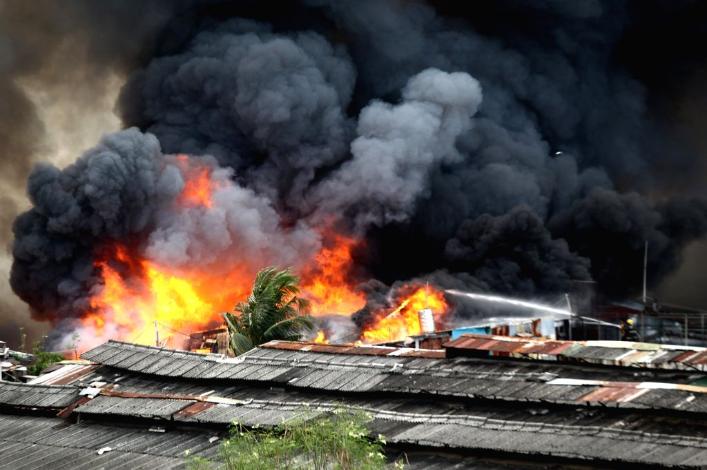 Photo taken on Jan. 1, 2015 shows a finger of black smoke billows from a fire that broke out at a residential area in Quezon City, the Philippines. The fire ...