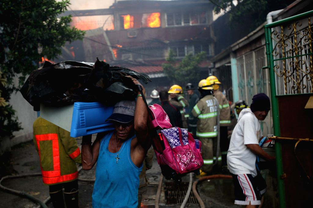 Residents evacuate with their belongings during a fire that broke out at a residential area in Quezon City, the Philippines, on Jan. 1, 2015. The fire razed more