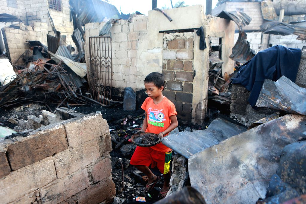 QUEZON CITY, Jan. 18, 2018 - A boy looks for reusable materials from burnt home after a fire that broke out at a residential area in Quezon City, the Philippines, on Jan. 18, 2018.