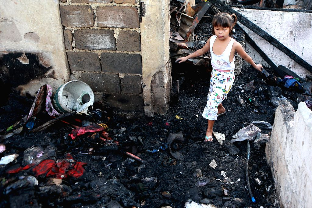 QUEZON CITY, Jan. 18, 2018 - A girl looks for reusable materials from burnt home after a fire that broke out at a residential area in Quezon City, the Philippines, on Jan. 18, 2018.