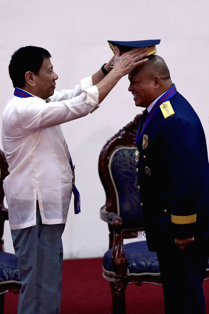 QUEZON CITY, July 1, 2016 - Philippine President Rodrigo Duterte (L) puts a new hat on National Police Chief Ronald dela Rosa during Ronald dela Rosa's assumption of command ceremony in Quezon City ...