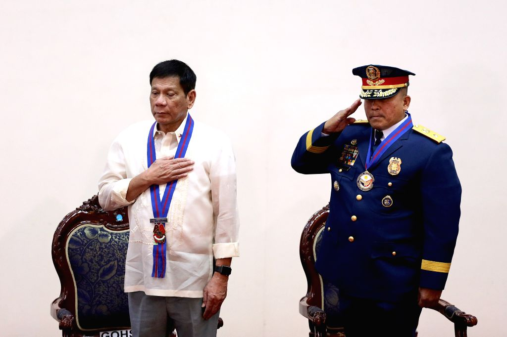 QUEZON CITY, July 1, 2016 - Philippine President Rodrigo Duterte (L) attends the assumption of command ceremony of National Police Chief Ronald dela Rosa (R) in Quezon City July 1, 2016.