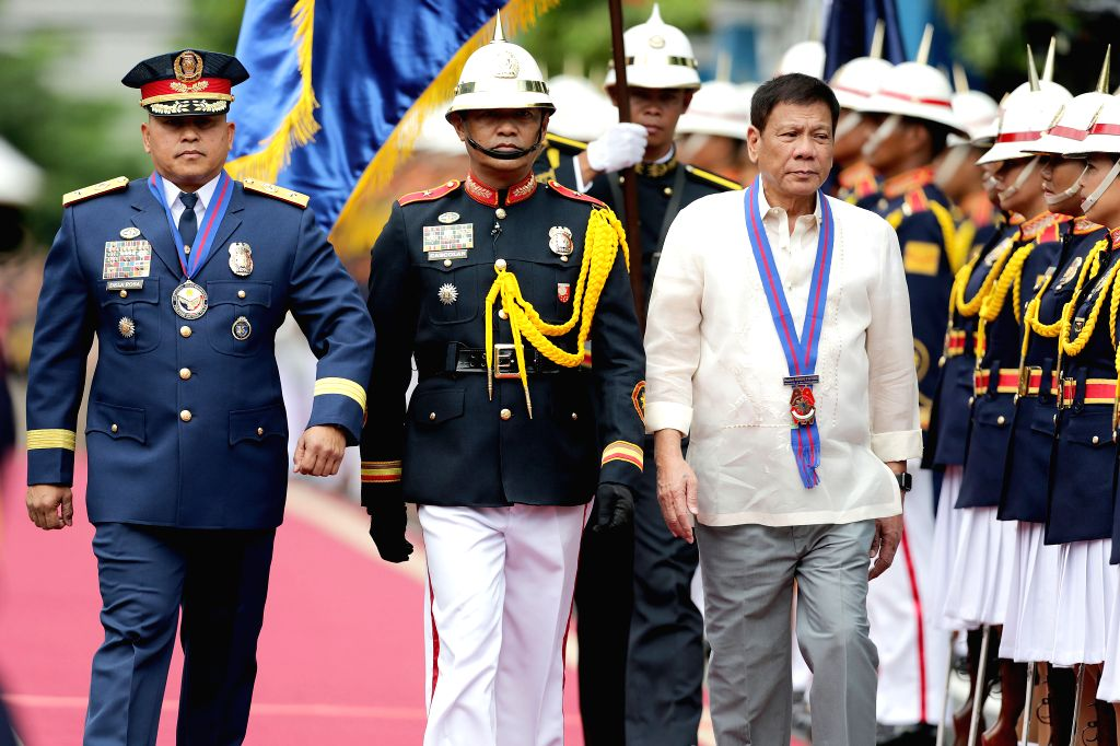 QUEZON CITY, July 1, 2016 - Philippine President Rodrigo Duterte (3rd L), accompanied by Philippine National Police Chief Ronald dela Rosa (1st L), during Ronald dela Rosa's assumption of command ...