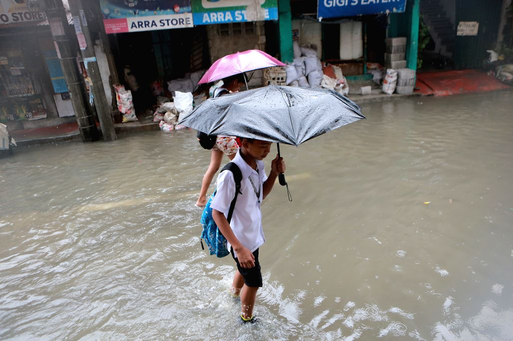 QUEZON CITY, July 17, 2018 - Residents wade through flood water brought by the heavy rain in Quezon City, the Philippines, July 17, 2018.