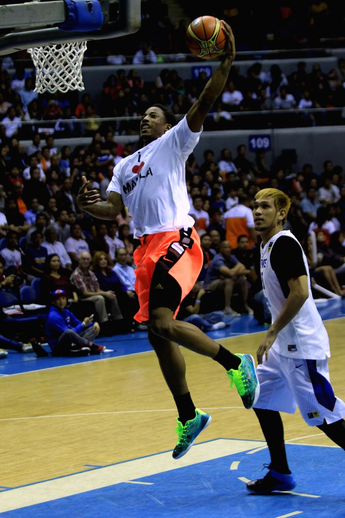 Demar DeRozan (Top) of the Toronto Raptors goes to the basket during a charity event in Quezon City, the Philippines, July 22, 2014. Nine NBA players ...