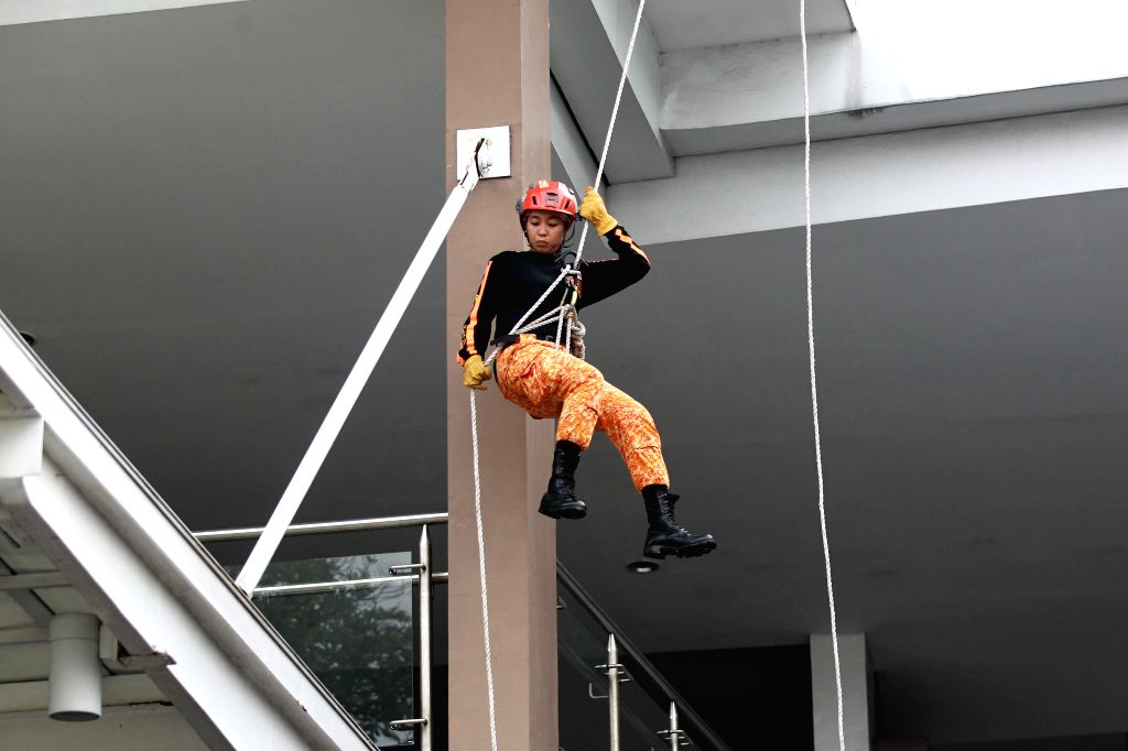 QUEZON CITY, July 27, 2019 - A member of the Philippine Bureau of Fire Protection (BFP) rappels down a building during the Nationwide Simultaneous Earthquake Drill in Quezon City, the Philippines, ...