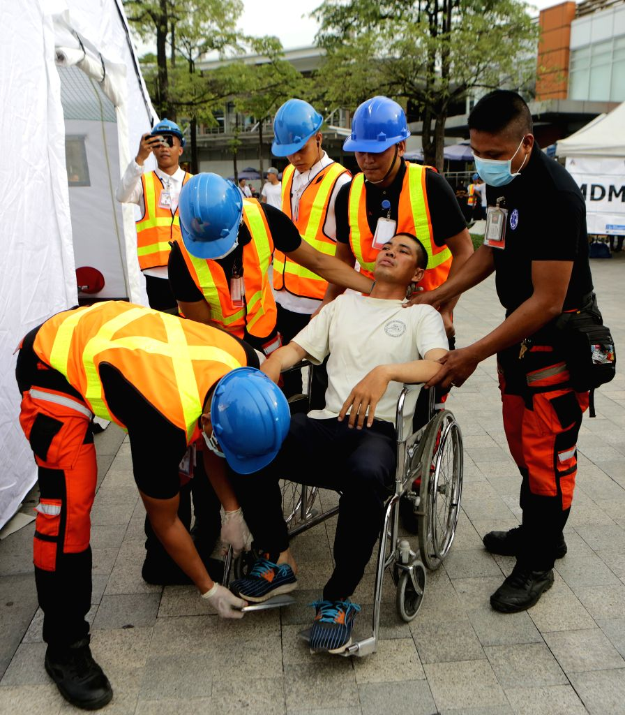 QUEZON CITY, July 27, 2019 - Rescuers attend to a mock victim during the Nationwide Simultaneous Earthquake Drill in Quezon City, the Philippines, July 27, 2019. The Metropolitan Manila Development ...