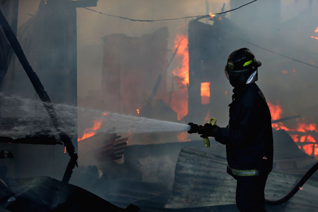QUEZON CITY, June 28, 2016 - A firefighter tries to put out a fire at a slum area in Quezon City, the Philippines, June 28, 2016. More than 300 shanties were razed in the fire, leaving 600 families ...