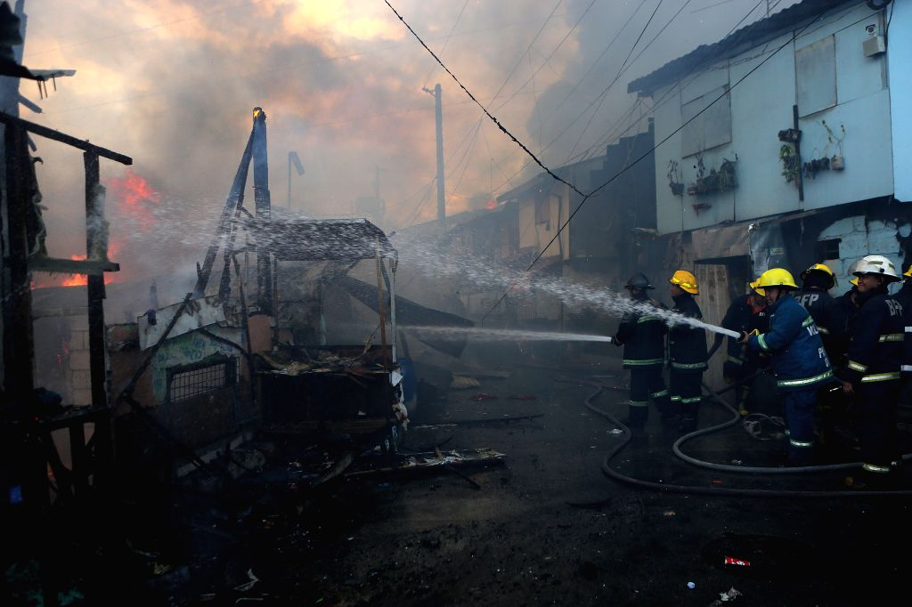 QUEZON CITY, June 28, 2016 - Firefighters try to put out a fire at a slum area in Quezon City, the Philippines, June 28, 2016. More than 300 shanties were razed in the fire, leaving 600 families ...