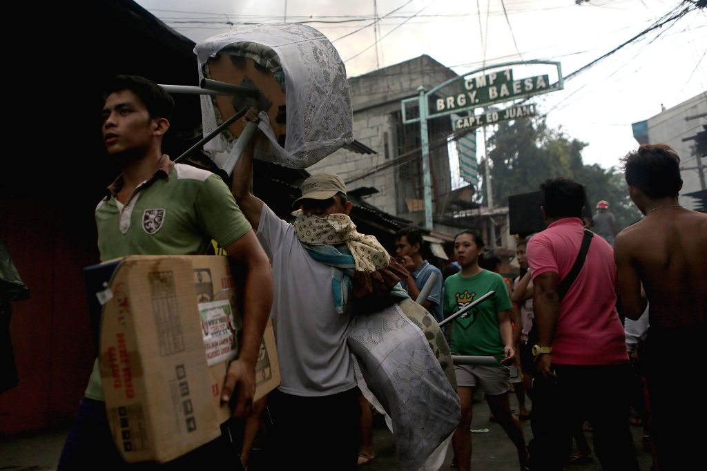 QUEZON CITY, June 28, 2016 - Residents evacuate with their belongings from a fire scene at a slum area in Quezon City, the Philippines, June 28, 2016. More than 300 shanties were razed in the fire, ...