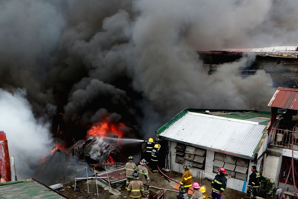 QUEZON CITY, March 5, 2019 - Firefighters try to put out a fire at a residential area in Quezon City, the Philippines, March 5, 2019.