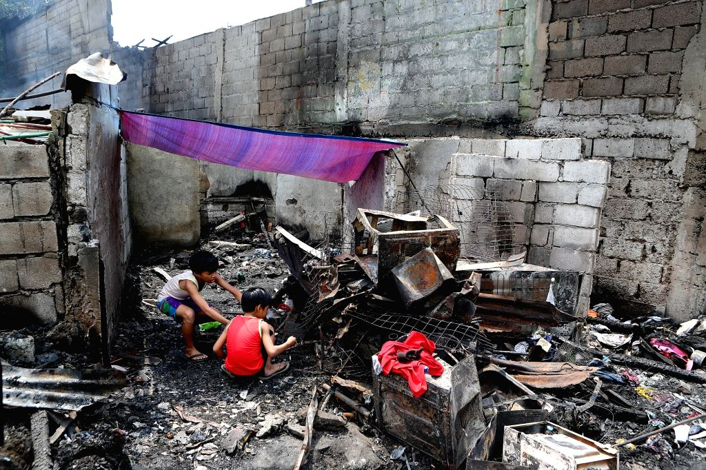 QUEZON CITY, March 6, 2019 - Children search for belongings from their charred homes after a fire at a residential area in Quezon City, the Philippines, March 6, 2019. Around 150 houses were razed in ...