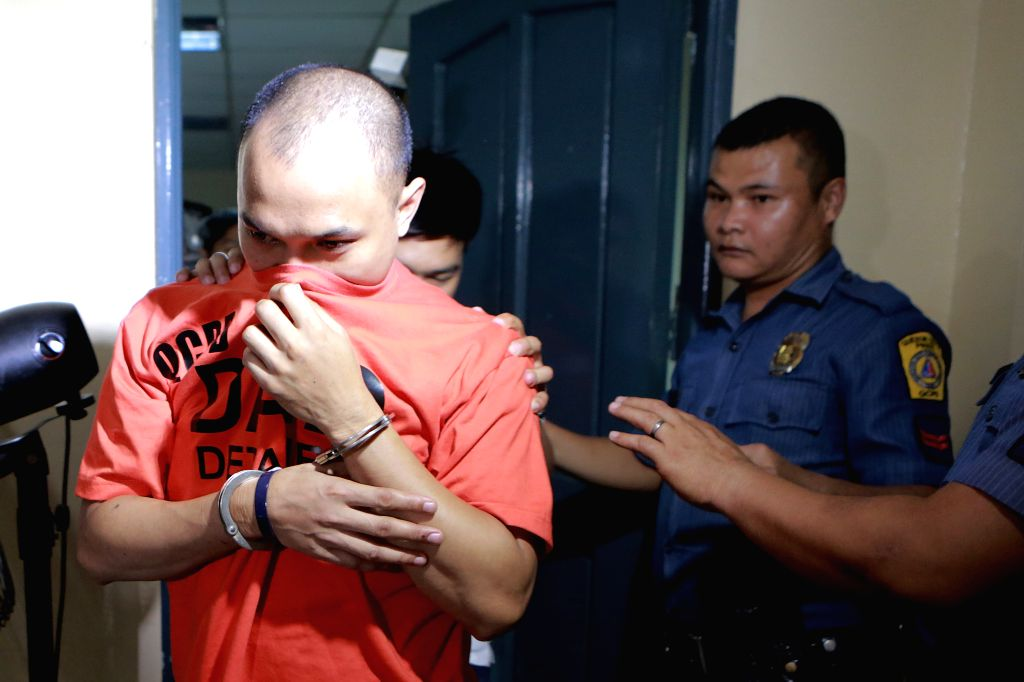 QUEZON CITY, Oct. 5, 2016 - An arrested illegal drug dealer covers his face during a press conference inside Camp Karingal in Quezon City, the Philippines, Oct. 5, 2016. Php2.79 million pesos worth ...