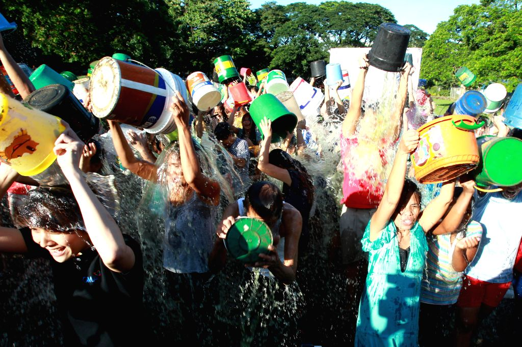 People dump cold water on their heads during the mass ice bucket challenge in Quezon City, the Philippines, on Sept. 7, 2014. More than 200 people took part in .