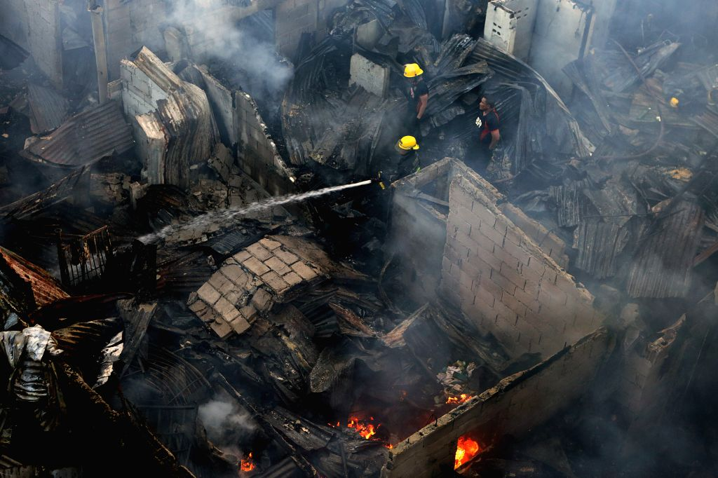 QUEZON, June 7, 2019 - Firefighters try to put out a fire at a slum area in Quezon City, the Philippines, June 7, 2019. More than 120 families were left homeless in the blaze.