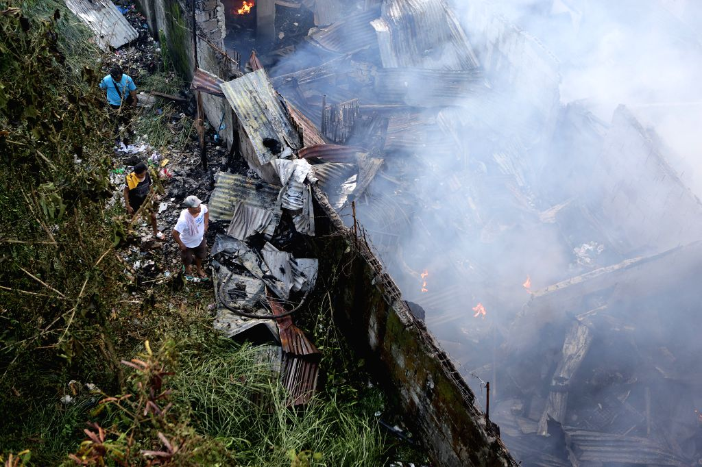 QUEZON, June 7, 2019 - Residents try to retrieve useful materials from their burning home during a fire at a slum area in Quezon City, the Philippines, June 7, 2019. More than 120 families were left ...