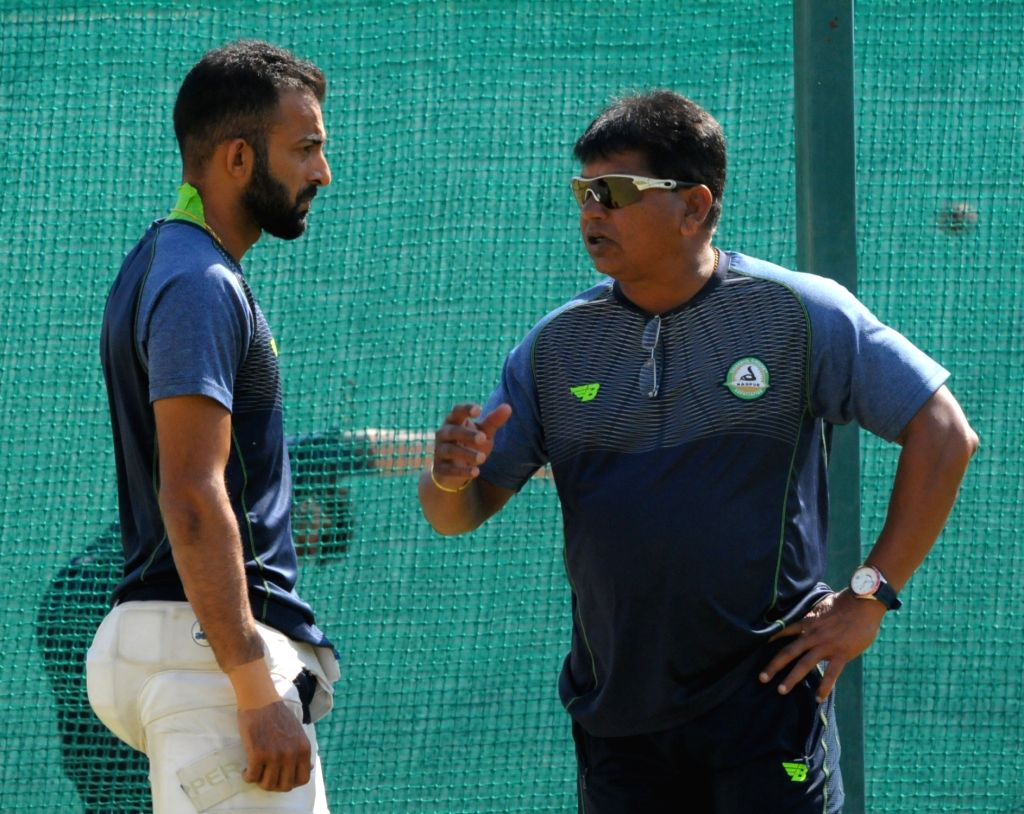 (R to L) Vidarbha Ranji team head coach Chandrakant Pandit interacts with skipper Faiz Fazal during a practice session ahead of their Irani trophy match against Rest of India in Nagpur on Feb ...