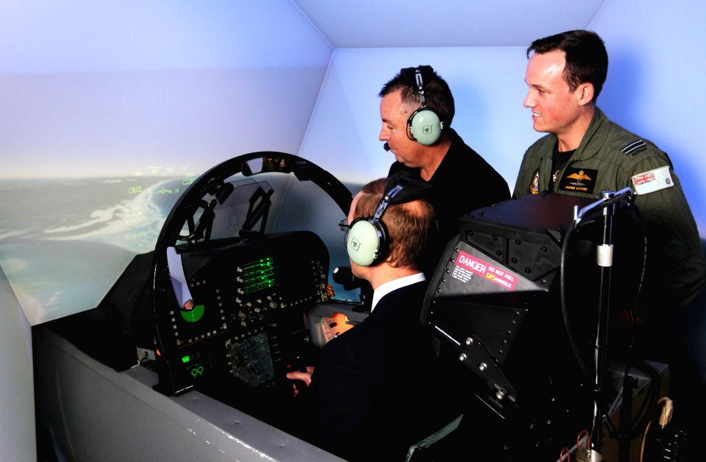 British Prince William (L) experiences a flight in the F/A18-F Super Hornet simulator under the guidance of Mike Prior, Training Services Manager for ...