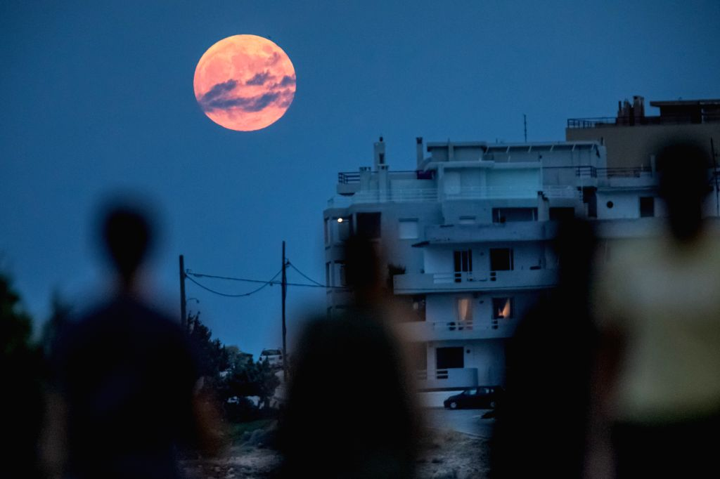 RAFINA, July 17, 2019 - Photo taken on July 16, 2019 shows a full moon rising on a cloudy day at Rafina in Greece.