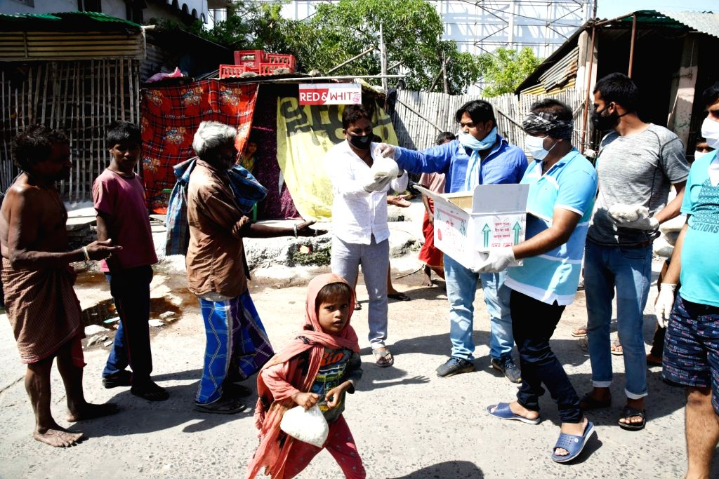 Railway employees distribute relief material among the poor and needy people on Day 7 of the 21-day nationwide lockdown imposed as a measure to contain the spread of  coronavirus, in Patna on ...