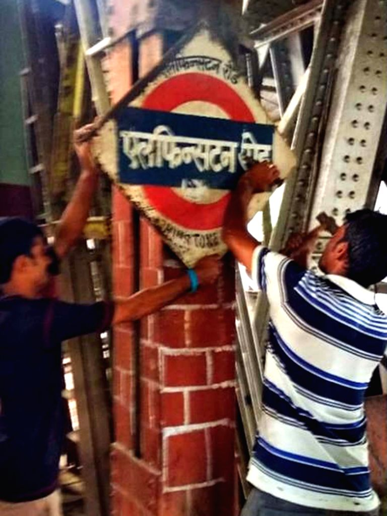 "Railway employees remove a board reading ""Elphinstone Road"" after it was renamed as ""Prabha Devi"" railway station in Mumbai, on July 18, 2018."