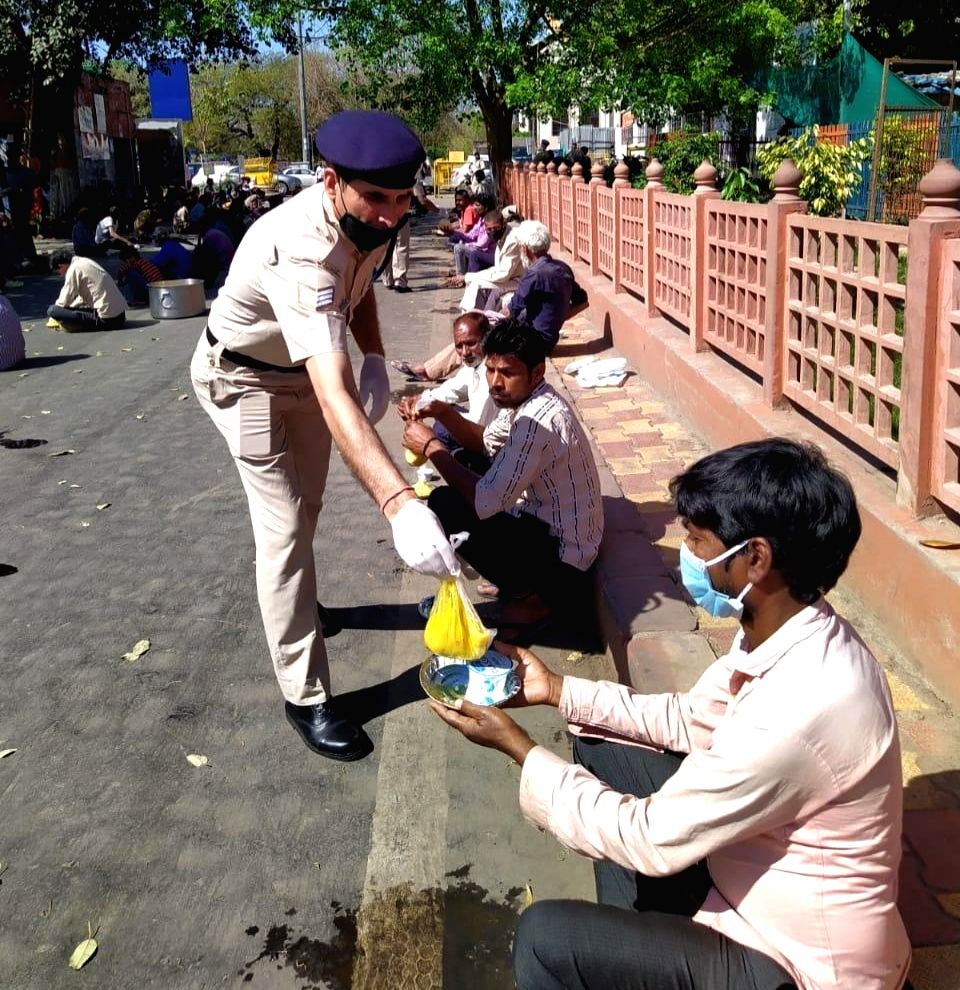 Railway Protection Force personnel distribute food among the poor and the needy on Day 4 of the lockdown imposed in the wake of the coronavirus pandemic, in New Delhi on March 28, 2020. Indian Railways is transporting essential commodities across Ind