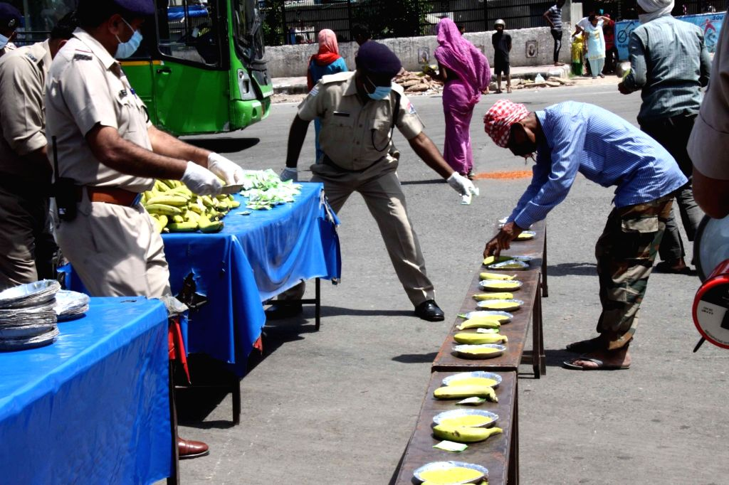 Railway Protection Force (RPF) personnel strictly practise social distancing as they distribute food among the poor and needy people at Delhi's Hazrat Nizamuddin railway station during the ...