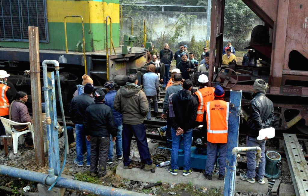 Railway workers work on the tracks after three bogies of the goods train derailed at the Patna junction; in Patna on Jan 16, 2018.