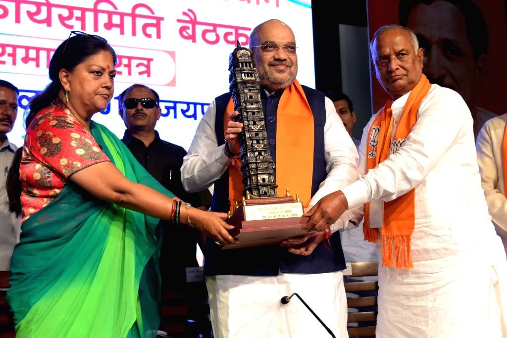 Rajasthan Chief Minister Vasundhara Raje and BJP State President Madan Lal Saini present a momento to BJP chief Amit Shah at a party meeting, in Jaipur on July 21, 2018. - Vasundhara Raje and Amit Shah