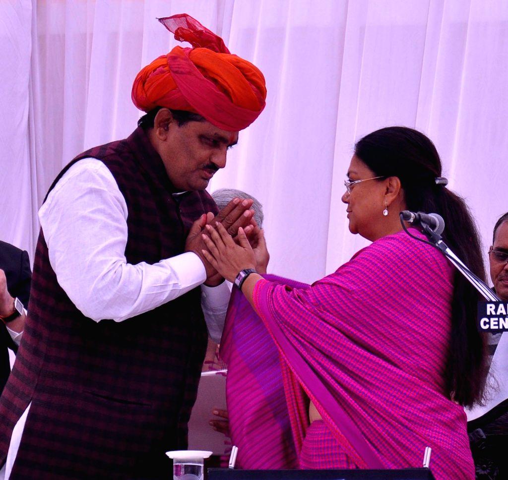Rajasthan Chief Minister Vasundhara Raje greets BJP leader Prabhulal Saini after he took oath as Cabinet Minister during a function at Raj Bhawan in Jaipur on Dec.20, 2013. (Photo: Ravi Shankar ...