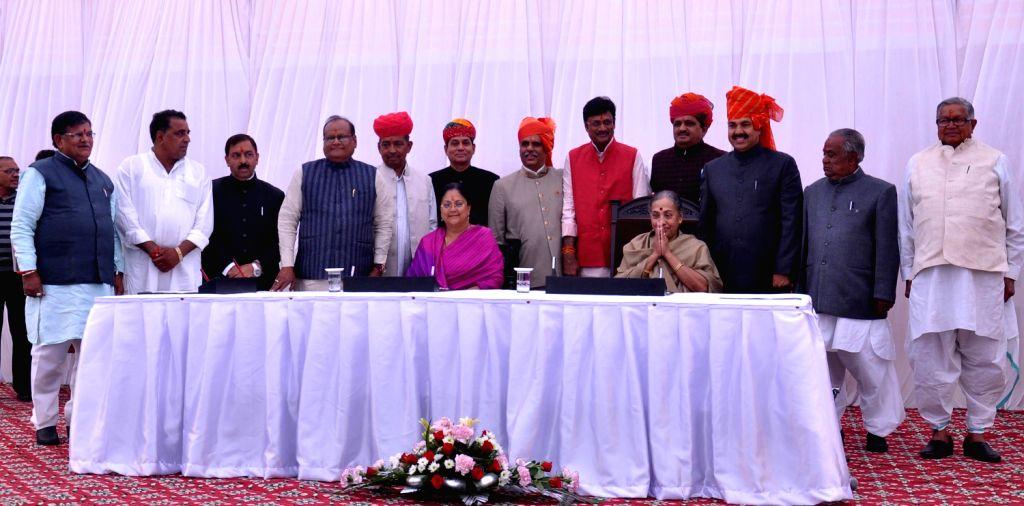 Rajasthan Chief Minister Vasundhara Raje greets BJP leader Gulab Chand Katariya after he took oath as Cabinet Minister during a function at Raj Bhawan in Jaipur on Dec.20, 2013. (Photo: Ravi Shankar .