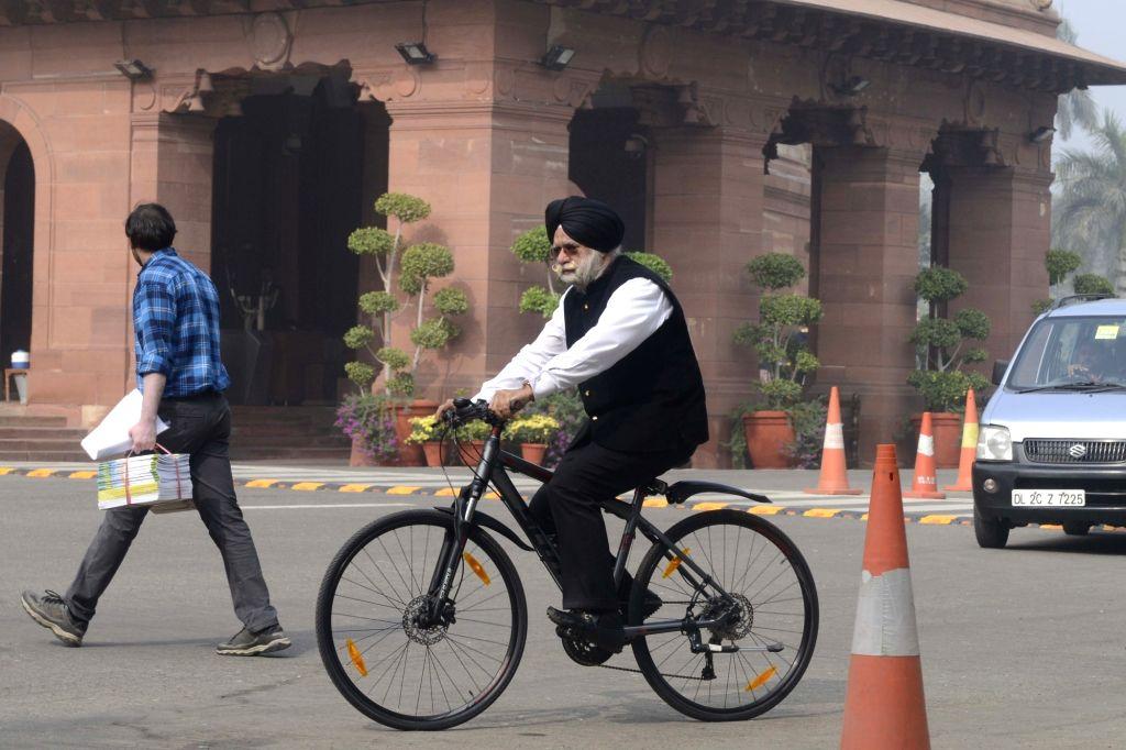 Rajya Sabha member K. T. S. Tulsi arrives at Parliament riding a cycle in New Delhi on Nov 30, 2016.