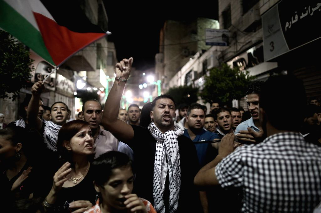 Palestinians take part in a protest in solidarity with Palestinian under the Israeli military offensive on Gaza Strip, in the West Bank City of Ramallah on July ...