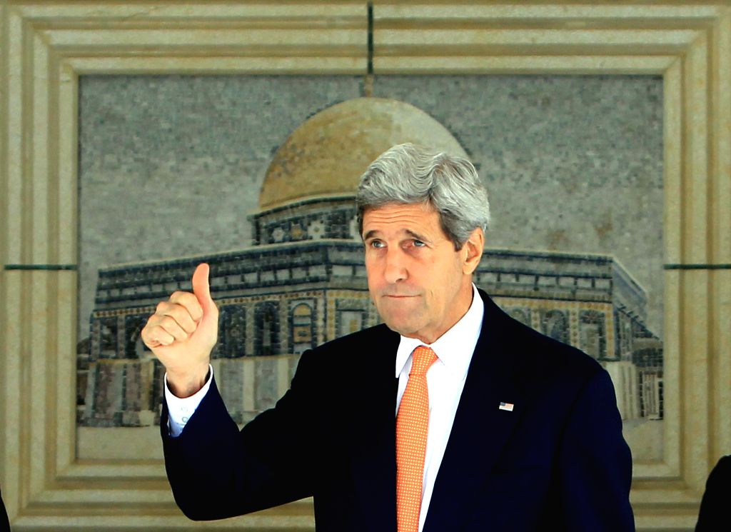U.S. Secretary of State John Kerry (front) waves to media upon his arrival for meeting with Palestinian President Mahmoud Abbas in the west bank city of Ramallah ..